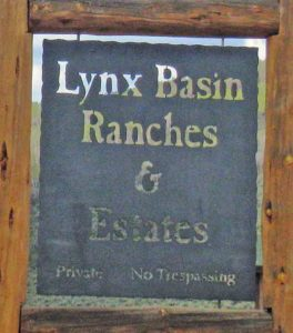 Metal entry sign saying Lynx Basin Ranches and Estates